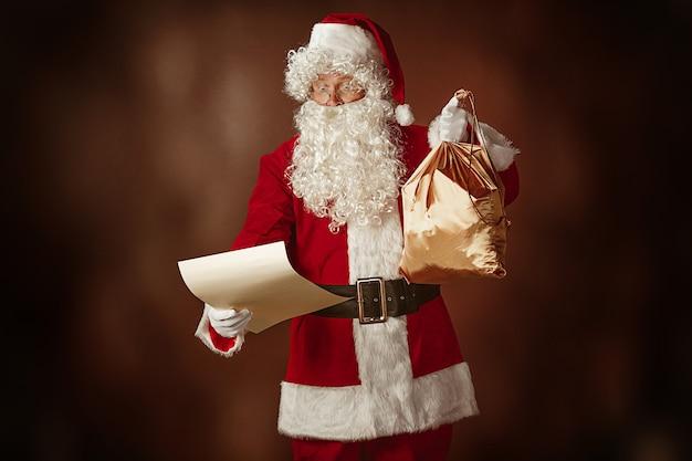 Портрет мужчины в костюме санта-клауса - с роскошной белой бородой, шляпой санта-клауса и красным костюмом читает письмо на красном фоне студии с подарками