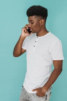 Портрет мужчины в футболке, говорящего по смартфону
