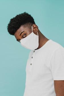얼굴 마스크를 착용하는 t- 셔츠에있는 남자의 초상화