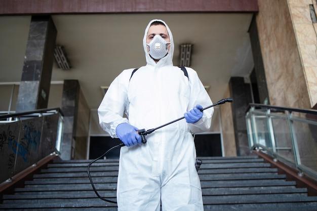 コロナウイルスとの戦いの準備ができている噴霧器タンクと白い防護服の男の肖像画