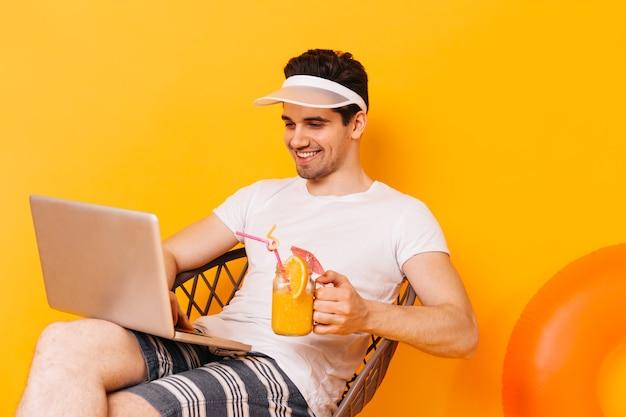 休暇中にラップトップで作業している白いtシャツの男の肖像画。男はオレンジカクテルを飲みます。