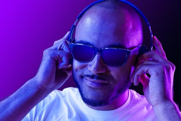Портрет мужчины, слушающего музыку в неоновом свете