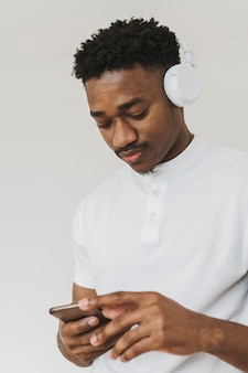 スマートフォンでヘッドフォンで音楽を聴いている男の肖像画
