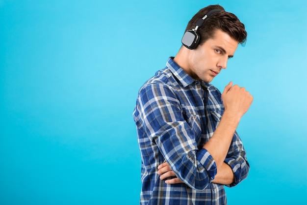 青で楽しんでいるワイヤレスヘッドフォンで音楽を聴いている男の肖像画