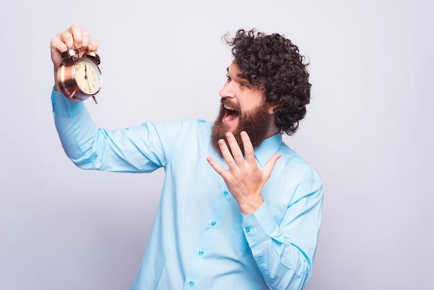 目覚まし時計を恐れて見ている男の肖像画