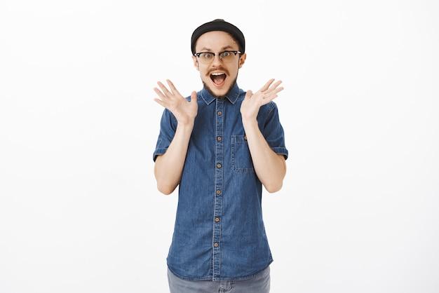 興奮からスピーチを失い、スリルを揺さぶる男の肖像が驚きと驚きの驚きから手を上げた