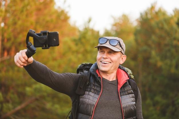 Портрет мужчины, снимающего видео и фото со смартфоном и стабилизатором в лесу