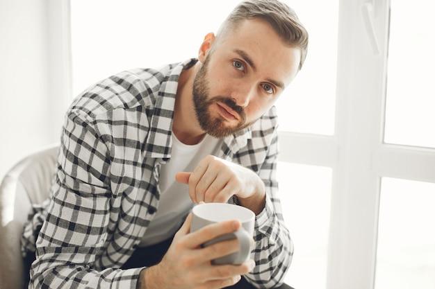 Портрет мужчины, расслабляющегося дома с чашкой кофе