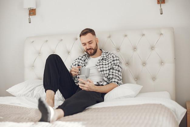 Портрет мужчины, расслабляющегося дома со смартфоном