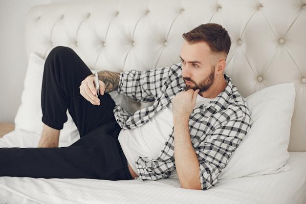 Портрет мужчины, расслабляющегося дома со смартфоном Бесплатные Фотографии