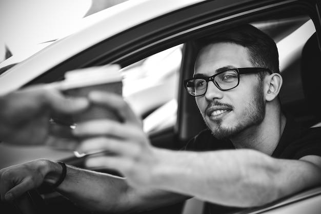 車に座って、行くためにコーヒーを買う男の肖像画