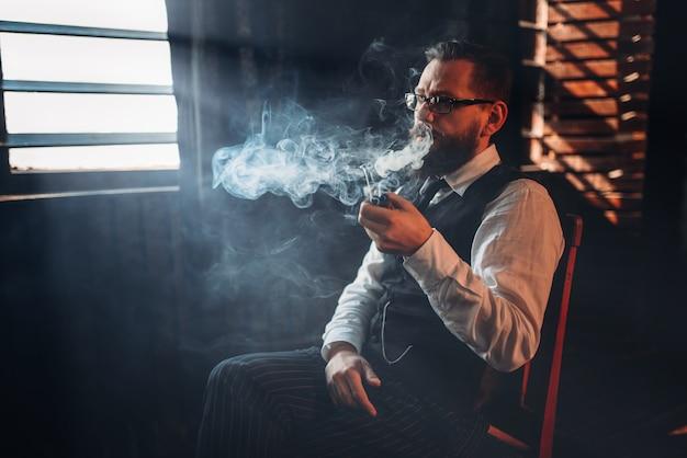 Портрет мужчины, сидящего на стуле и курительной трубки