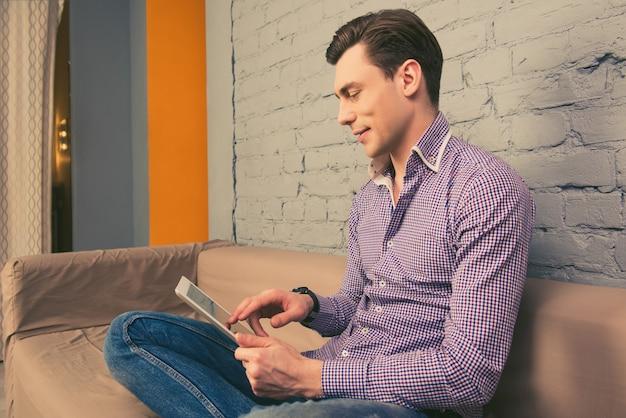 ソファに座ってタブレットでニュースを読んでいる男の肖像画