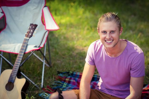キャンプ場で草の上に座っている男の肖像