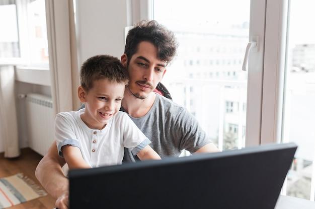 집에서 노트북을 사용하는 그의 웃는 아들과 함께 앉아 남자의 초상