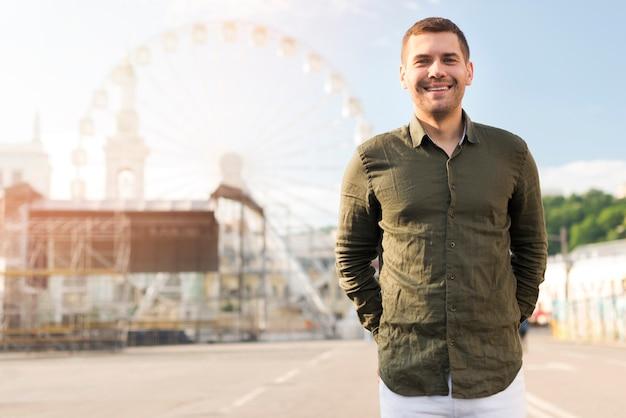 Портрет человека, стоящего возле колеса обозрения в парке развлечений
