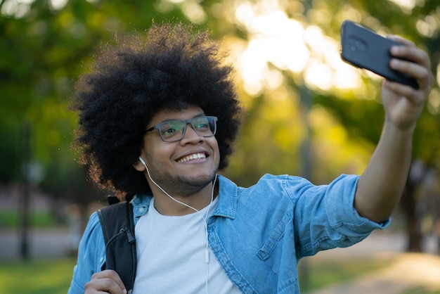 Портрет мужчины, делающего селфи со своим мобильным телефоном, стоя на улице на улице