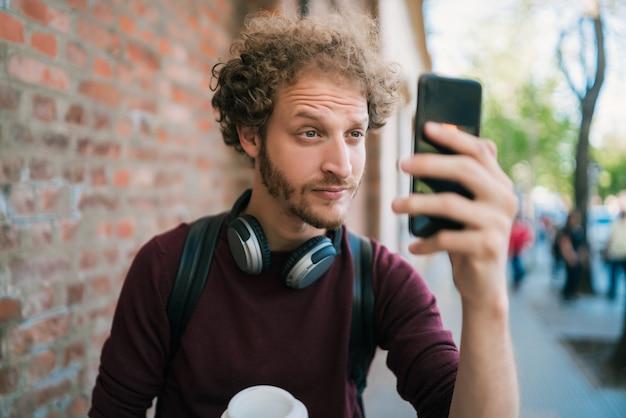 通りの屋外で彼のmophile電話で自分撮りをしている男の肖像画。技術コンセプト。