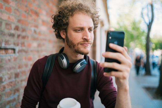 通りの屋外で彼のmophile電話で自分撮りをしている男の肖像画。