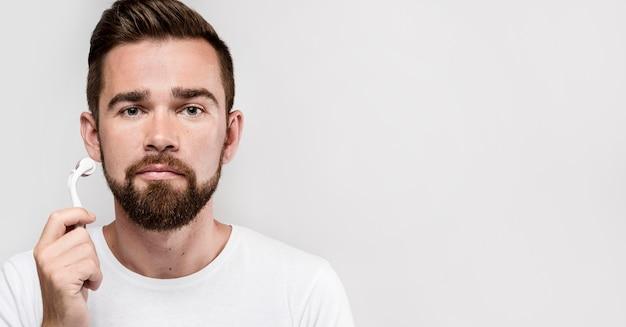 Портрет мужчины, использующего ролик для лица с копией пространства