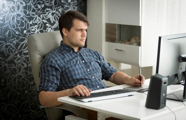 オフィスでデジタルグラフィックタブレットとキーボードを使用して男の肖像画