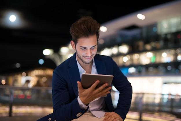 Портрет человека, используя его планшет в городе в ночное время