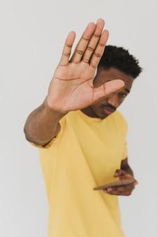 スマートフォンを使用して停止を示している男の肖像画