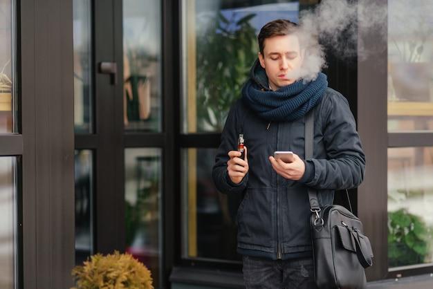屋外で気化器を払う男性の肖像画。安全な喫煙。