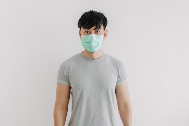 男性の肖像画は、白い背景で隔離のマスクを着用します。