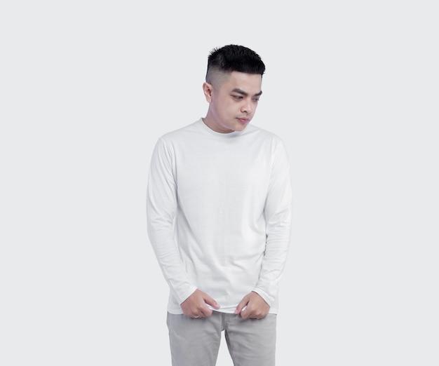 無地の背景に白い長袖tシャツを着ている男の肖像画