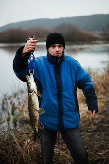 Портрет человека, взвешивающего пойманную рыбу возле озера