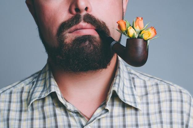 その中にバラの花を持つひげと煙パイプを持つ男の肖像