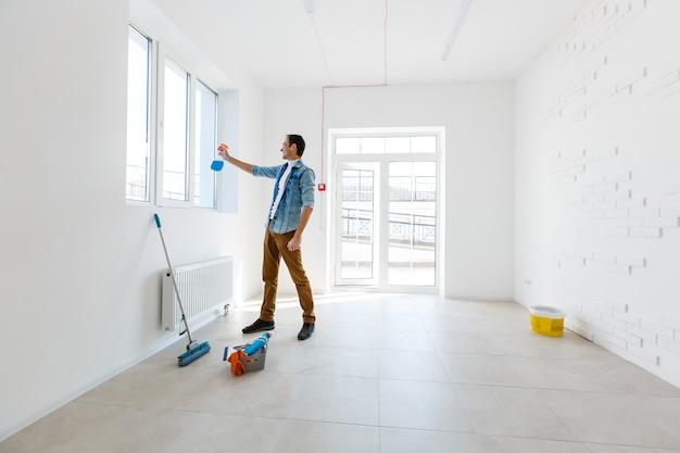 Портрет мужчины с уборочным оборудованием, убирающим дом