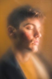 目を閉じてクローズアップを持つ男の肖像