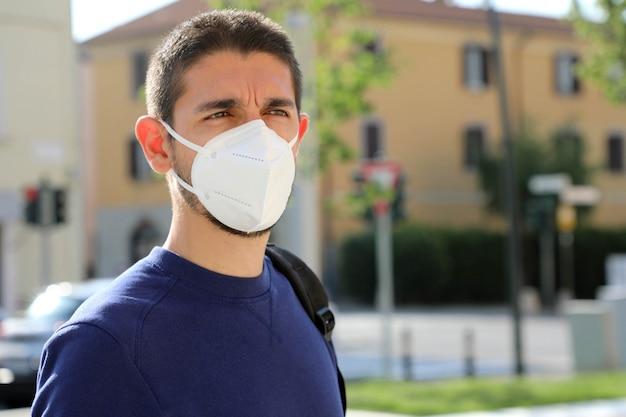 Sars-cov-2に対するフェイスマスクを持つ男の肖像。