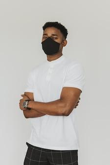 Портрет мужчины с маской для лица и скрещенными руками