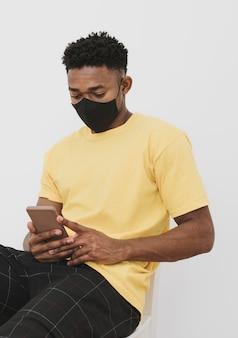 フェイスマスクとスマートフォンを持つ男の肖像画