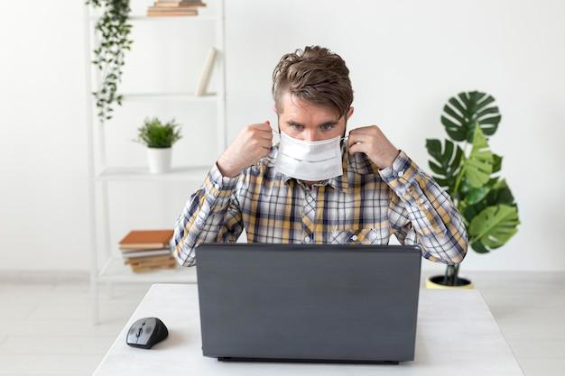 Портрет мужчины с маской, работающей на ноутбуке