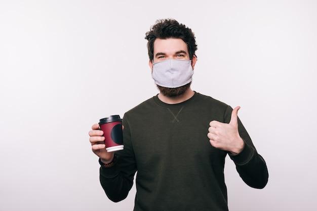 Портрет мужчины с маска для лица, держа чашку кофе и показывает палец вверх