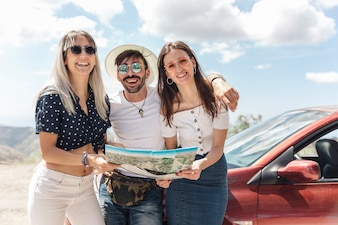 Portrait of man with female friends standing near the car