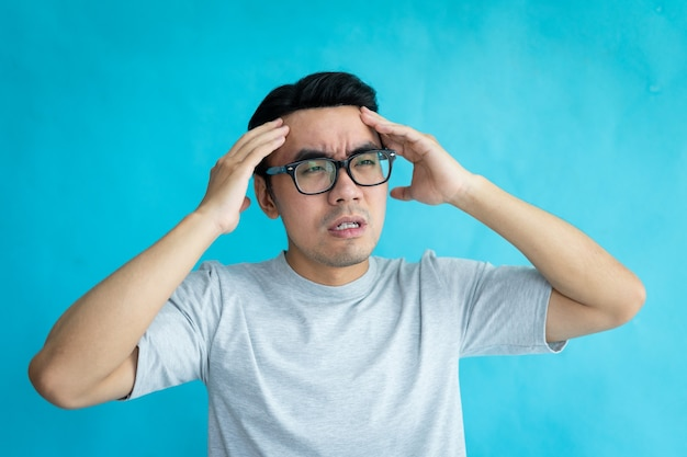 青い背景で隔離の頭痛と男の肖像画