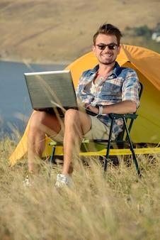노트북을 가진 남자의 초상화입니다. 캠핑 모험