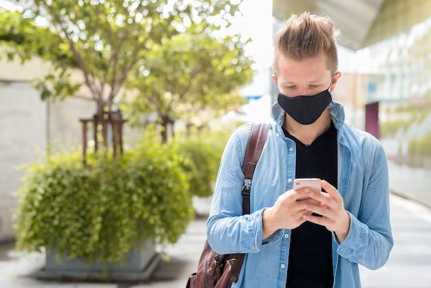 Портрет мужчины с маской, разговаривающего по телефону на улицах города на открытом воздухе