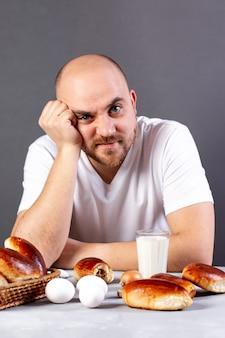 食事の前に食欲のない男の肖像画。食欲不振の概念。