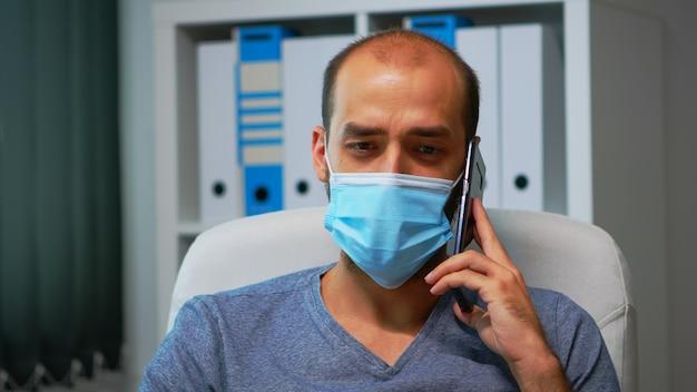 Covid-19の間にオフィスのモダンな部屋でパートナーと電話で話している保護マスクを持つ男の肖像画。スマートフォンで話す書き込みをチャットする新しい通常の職場で働くフリーランサー。