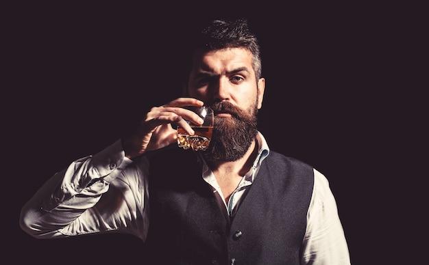 厚いひげを持つ男の肖像画。マッチョな飲酒。古いウイスキーのグラスを持っているスタイリッシュな金持ち。ひげを生やした紳士はコニャックを飲みます。最高級のウイスキーを飲みます。