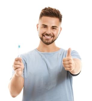 Портрет мужчины с зубной щеткой, показывая большой палец вверх на белом