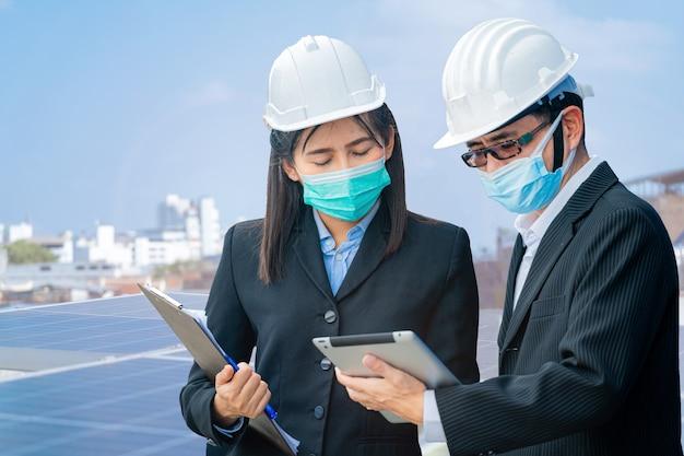 태블릿 장치를 사용하고 옥상에서 회의를 하는 남자 여자 엔지니어와 근로자의 초상화