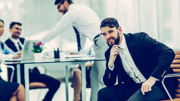 Портрет менеджера на фоне бизнес-команды, работающей я