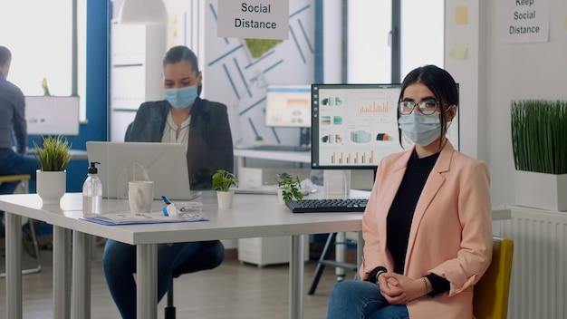 Nre通常の事業会社のオフィスの机のテーブルの椅子に座っているフェイスマスクを持つマネージャーの肖像画。コロナウイルスパンデミック時の社会的距離を尊重するバックグラウンドで働くチームワーカー